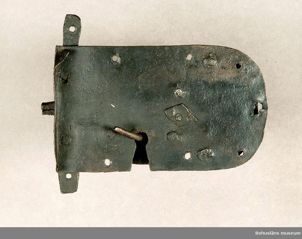 Ur handskrivna katalogen 1957-1958: Järnlås L.22,3 cm. Br. c:a 13,3 cm. Ålderdomlig typ. Nyckel saknas. Något.defekt.