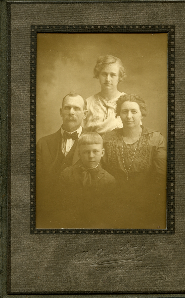 Portrett av en familie foran lerret. Familien består av to barn og mor og far. De er alle ikledd finklær.