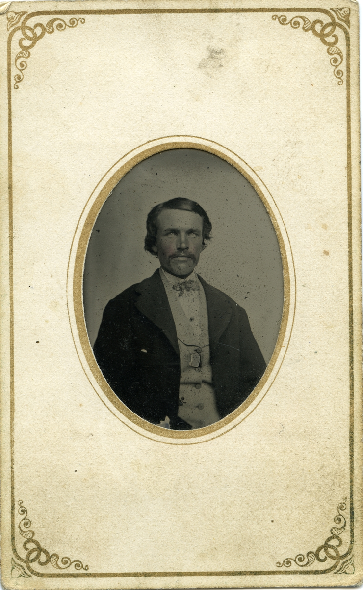 Portrett av mann foran lerret. Mannen er iført dress med vest og tørkle i halsen.