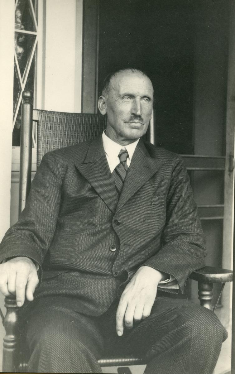 Portrett av en mann iført dress og slips. Mannen sitter i en stol foran en dør med vindu.