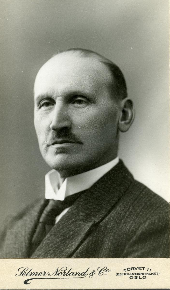 Portrett av mann. Mannen er iført dress med slips og hvit skjorte.