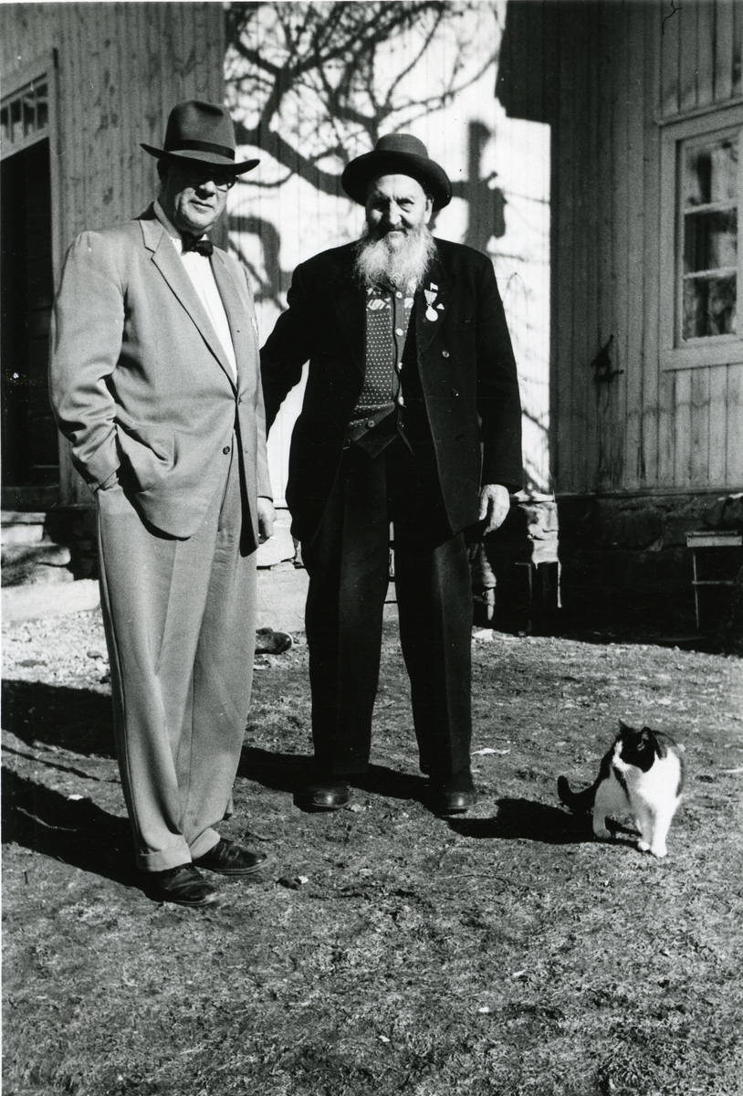 To menn iført hatt står foran noen trehus. Den ene mannen er iført dress mens det andre mannen er iført mer avslappede klær. En svart og hvit katt har også kommet med på bildet.