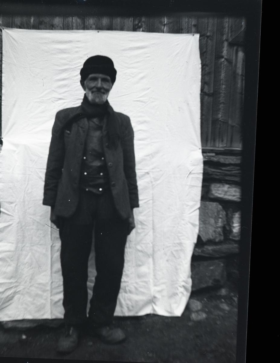 Portrett i helfigur av Ola Stølen, Vang, som står foran et laken som er stifta opp på en vegg/grunnmur. Ola er villreinsjeger