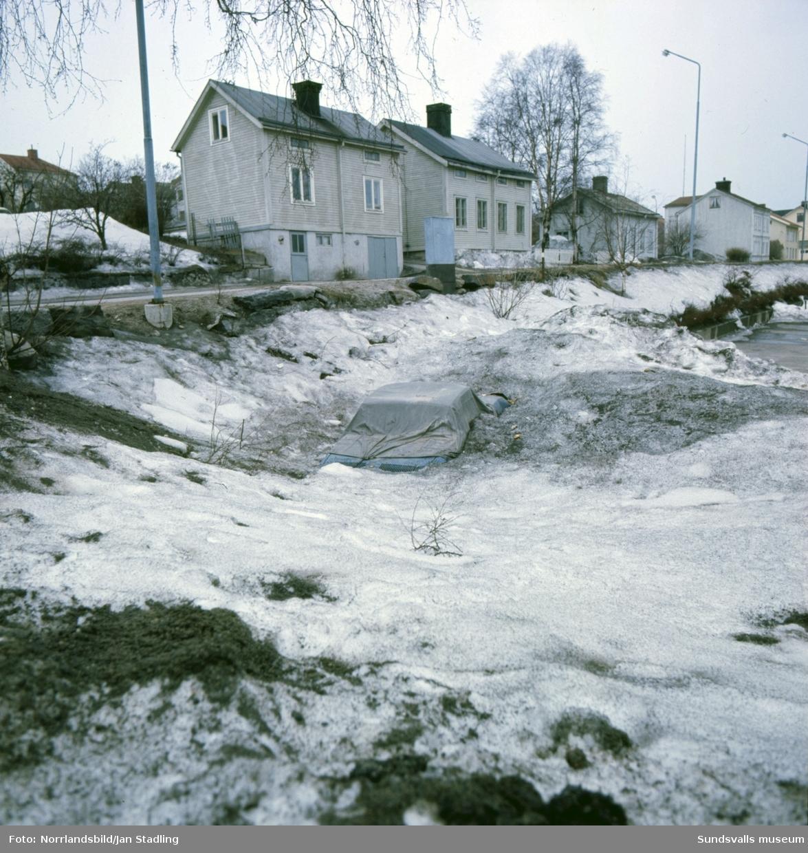 En översnöad bil tinar fram på en parkering på Södermalm våren 1977. Träkåkarna som syns på Nybrogatan och Nygatan finns fortfarande (2015) kvar.