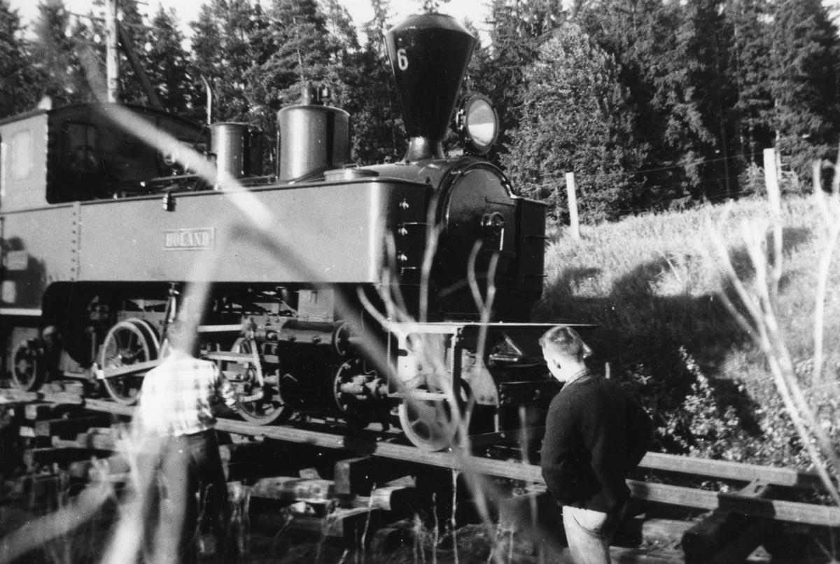 Damplok 6 Høland under transport fra Sørumsand verksteds område til museumsbanen. Transporten måtte gå via Løken i Høland pga. lav bru i Sørumsand. Her rulles lokomotivet av ved Sætra planovergang.