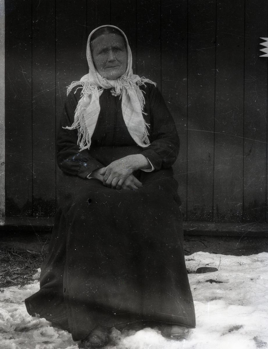 Kvinne avbildet i helfigur. Hun sitter på en stol, utenfor en husvegg, med snø på bakken. Hun er kledd i mørk kjole, og har et hvitt skaut på hodet og sølje i halsen.