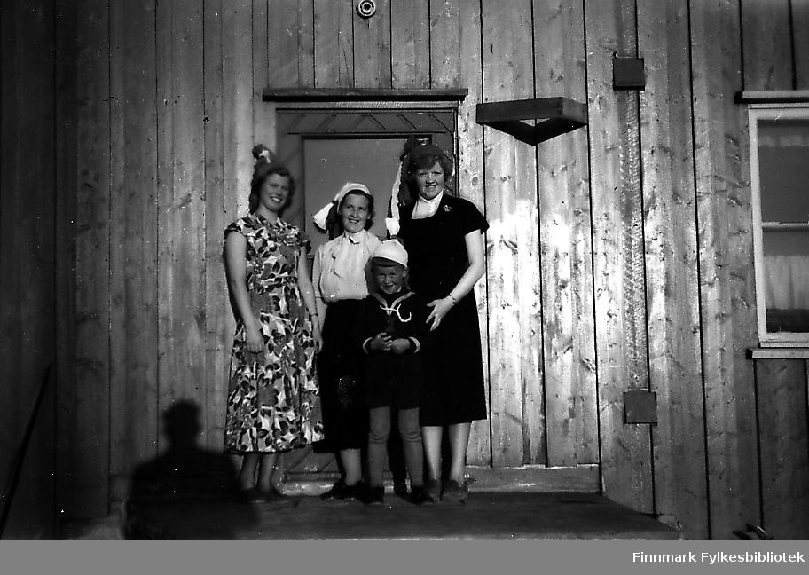 Tre damer og en gutte står på trappa. Kvinnene har kjoler på seg, det er 17.mai og dagen er solig og fin. Gutten heter Bjørn Ottar Betten og er kled i matroseskjorte og knebukser. Kvinnene fra venstre:frøken Birkeland, Gjerdrud Betten og frøken Bye. Alle tre jobbet som lærerinner på Seida skole i 1955.