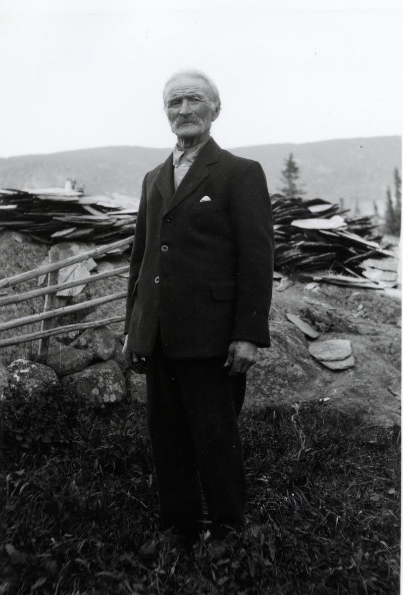 Elre mann i helfigur stånde foran en haug med skifertakstein. Han er kledd i mørk dress og skjorte uten slips.