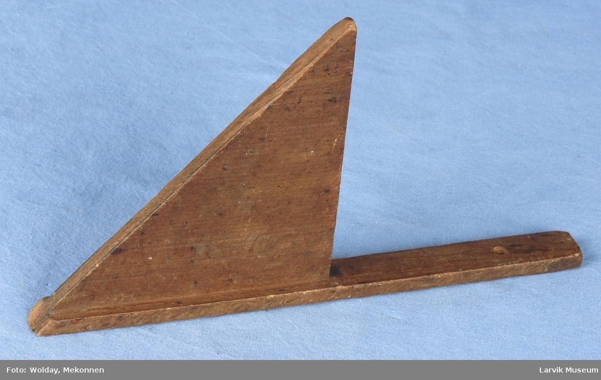 Form: En smal list er påmontert en trekant med to rette sider og en skrå. Hull øverst i listen.