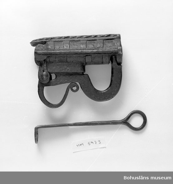Ur handskrivna katalogen 1957-1958: Järnlås Bultlås. L. c:a 17 cm. Br. c:a 5,5 cm. Nyckelns l. c:a 21,5 cm. br. c:a 2,5 (= största br.) Låset ngt rostigt.