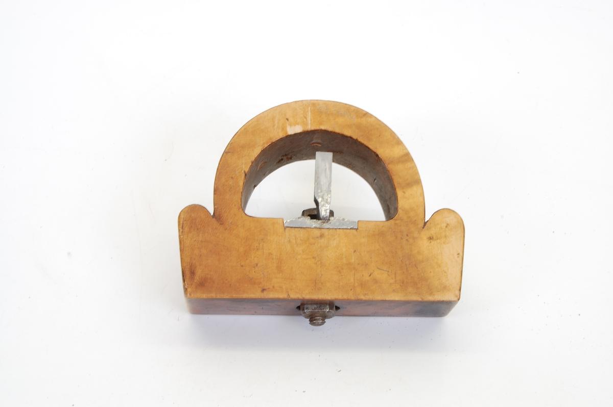 Form: rektangulær kloss med en halvmåneformet bue over. inni buen sitter høveljernet