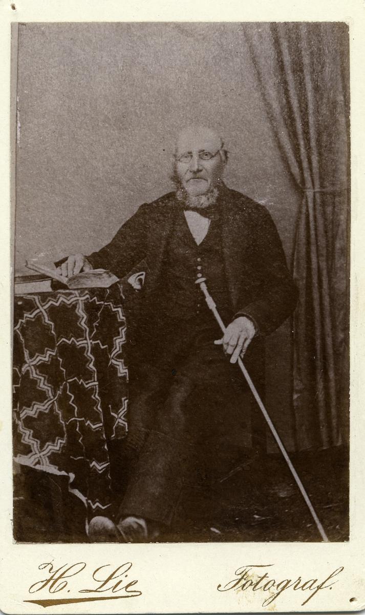 Portrett av mann sittende ved et bord. Mannen er iført dress med en stokk i hånden. Den andre hånden hviler på en bok.