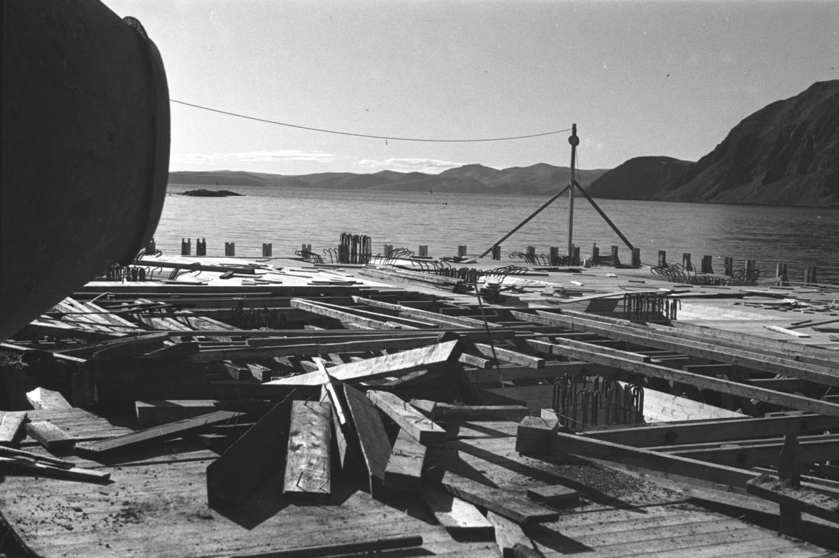 En kai under bygging i Honningsvåg like etter andre verdenskrig.  Ola Hanche-Olsen som har tatt bildene er født 13. mars 1920 i Borre, død 11. februar 1998 i Gjettum. Han var arkitekt og barnebokforfatter. Han hadde artium fra 1939, arkitekteksamen fra NTH 1946 og arbeidet deretter ved Finnmarkskontoret 1946–48 før han etablerte egen arkitektpraksis. Han debuterte som barnebokforfatter i 1974 med lettlestboka Knut og sjørøverne, og skrev i alt 12 bøker. Han var XU-agent 1944-45, og var også en aktiv fjellklatrer og friluftsmann. Ola var gift med Solveig Hanche-Olsen (f. Falkenberg); de fikk 3 barn, blant dem matematikeren Harald Hanche-Olsen.  Arkitektene Solveig og Ola Hanche-Olsen arbeidet ved Brente Steders Reguleringskontor i 1946. Hovedadministrasjon for gjenreisning av Nord-Troms og Finnmark ble lagt til Harstad og fikk navnet Finnmark kontoret. Landsdelen Nord-Troms og Finnmark blev oppdelt i syv distrikt med hver sin administrasjon. Honningsvåg, distrikt IV, skulle betjene Nordkapp, Lebesby, Porsanger og Karasjok kommune