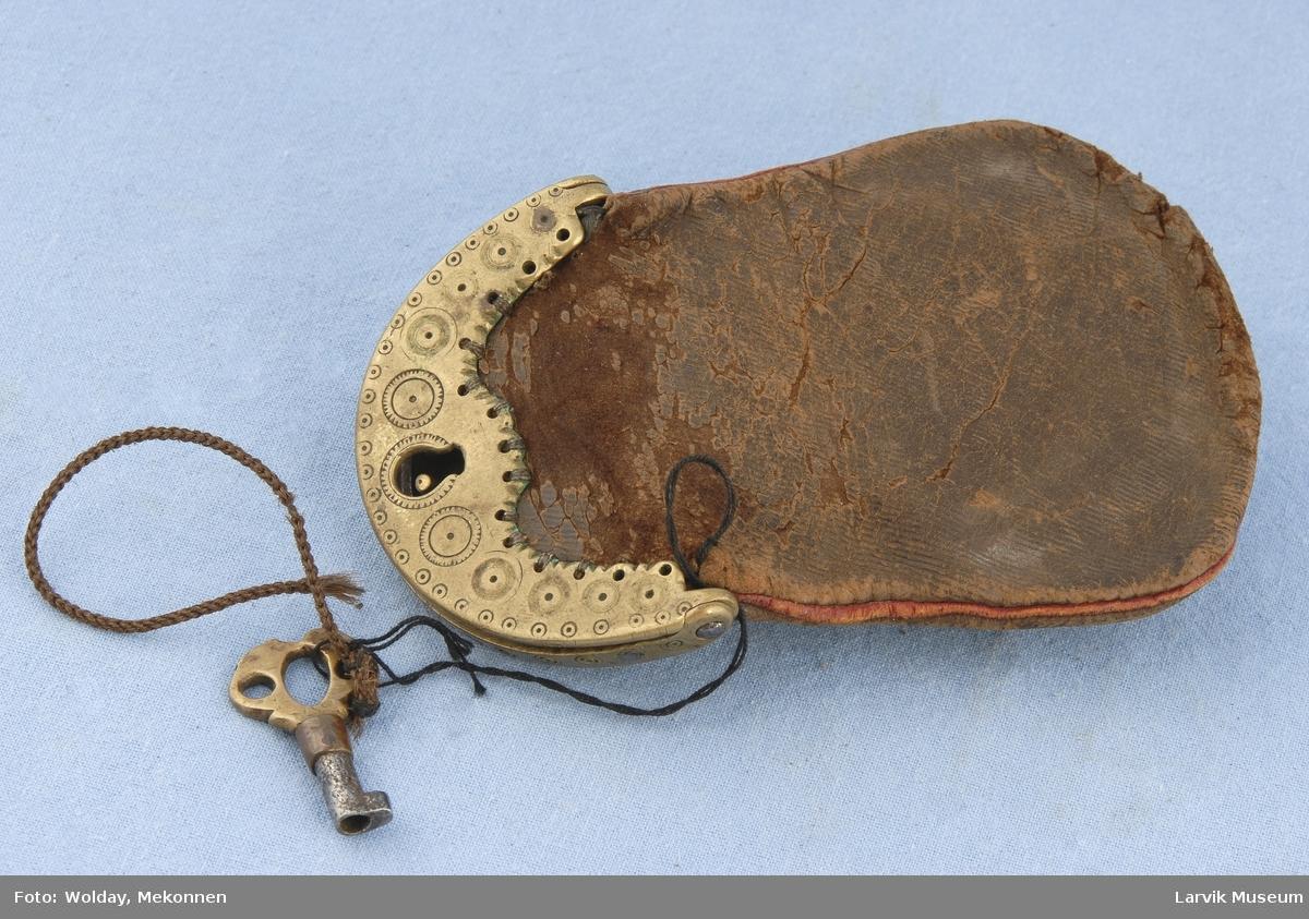 Form: En pung buet i bunnen. Messing lås med nøkkel hull og nøkkel. Sirkel mønster på låsen.