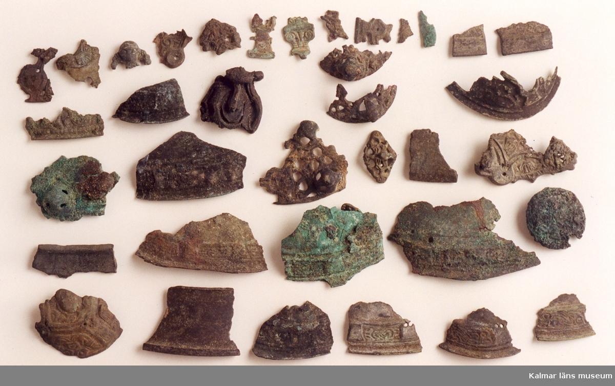 KLM 246. Bronsbitar m.m.  Ca tjugo bitar av ovala spännbucklor, såväl enskaliga som dubbelskaliga. Fem bitar av olika bronskärl, alla tillhörande övre kanten. Ingår i en samling föremål KLM 246 - 254, 848-869, 871, 889, 891.