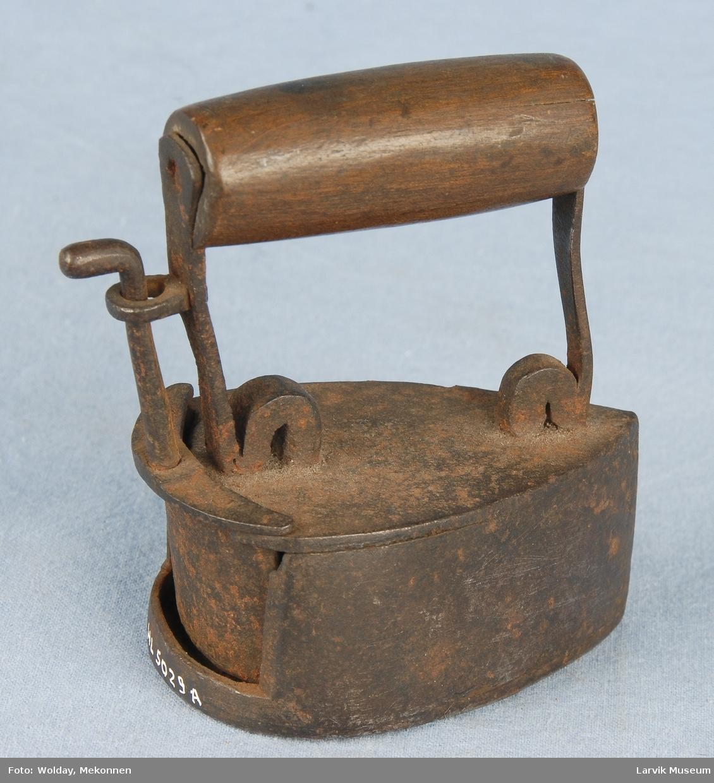 Form: Trekantet, buet, hul,  enkel. Håndtak i tre. Lite. varmebolt inni. Med bolt som varmes opp. lite, muligens for barn.