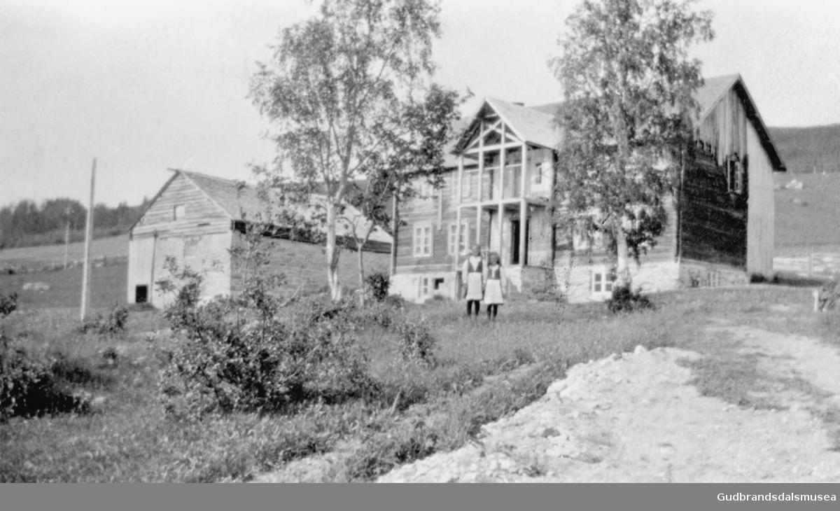 To små jenter i hagen foran huset, to bygninger, en vei går opp til gårdstunet, det er sommer i Søre Knipa.