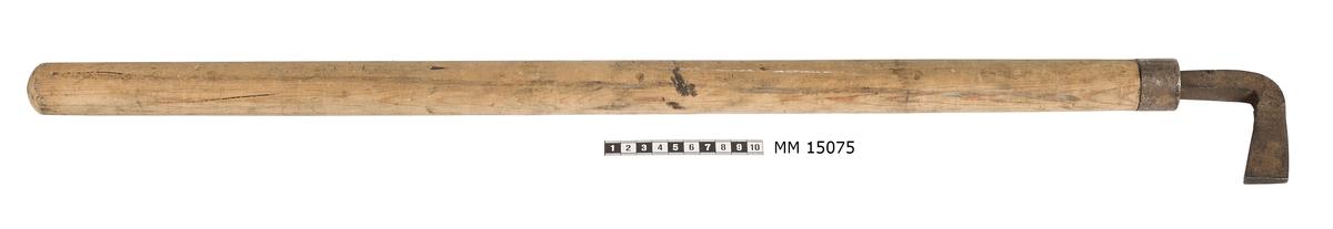 Nåthake av järn med träskaft. Haken av omålat järn, som är böjt i spetsig vinkel. Träskaftet är runt och obehandlat. Vid järnets fastsättning till skaftet finns en spännring.