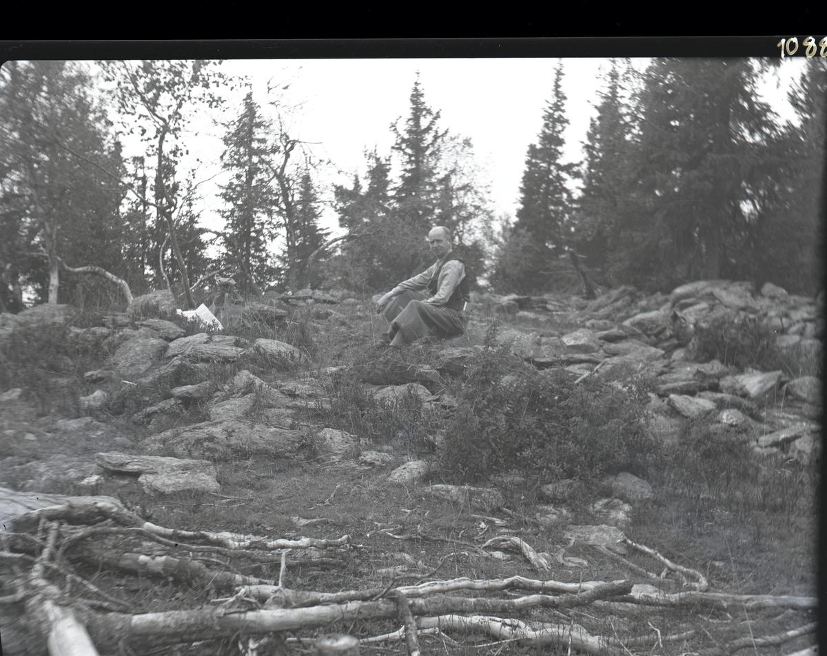 En mann avbildet midt i en steinhaug. Mannen er iført skjorte og vest. Rundt ham er det skog og trær. I baklommen har han en bok og sekken hans ligger til venstre i bildet sammen med et kart.