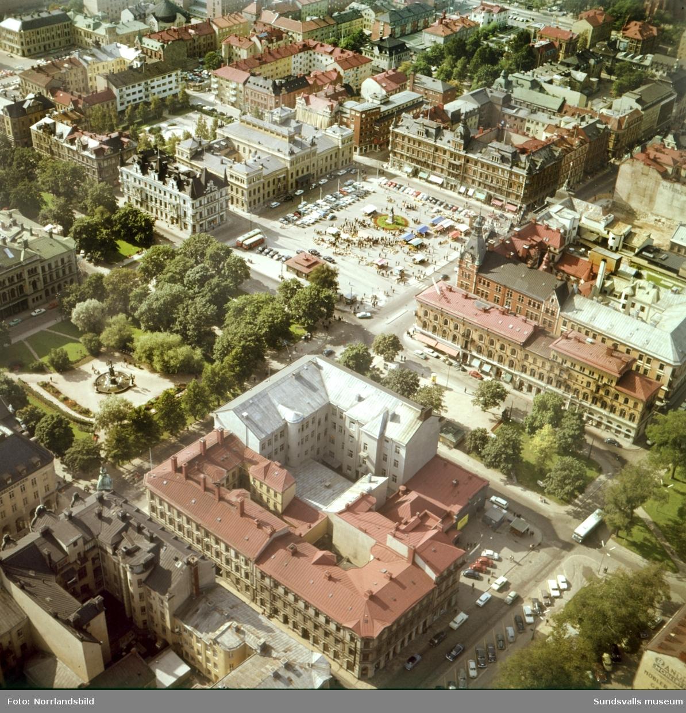 Flygfoto över Stenstaden med kvarteret Olympen närmast där biografen Röda Kvarn syns till höger. Vängåvan, Stora torget, Stadshuset och till höger syns rivningstomten i hörnet av Storgatan-Torggatan.