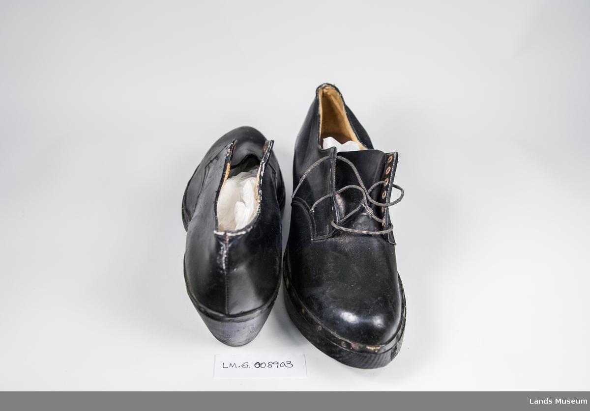 Sko i skai med papirtekstil fòr og tre såle. Pløse og snøring. Pløsen er skåret av på den ene skoen.
