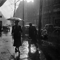 Paris. Fotgängare med paraply på regnig gata.