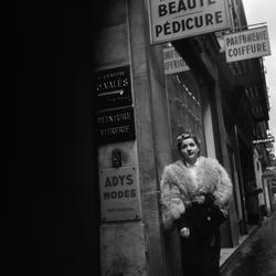 Paris. Kvinna i päls på gata utanför skönhetssalong.