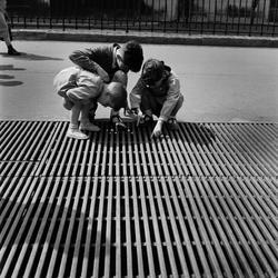 Paris. Tre pojkar leker på ett ventilationsgaller.
