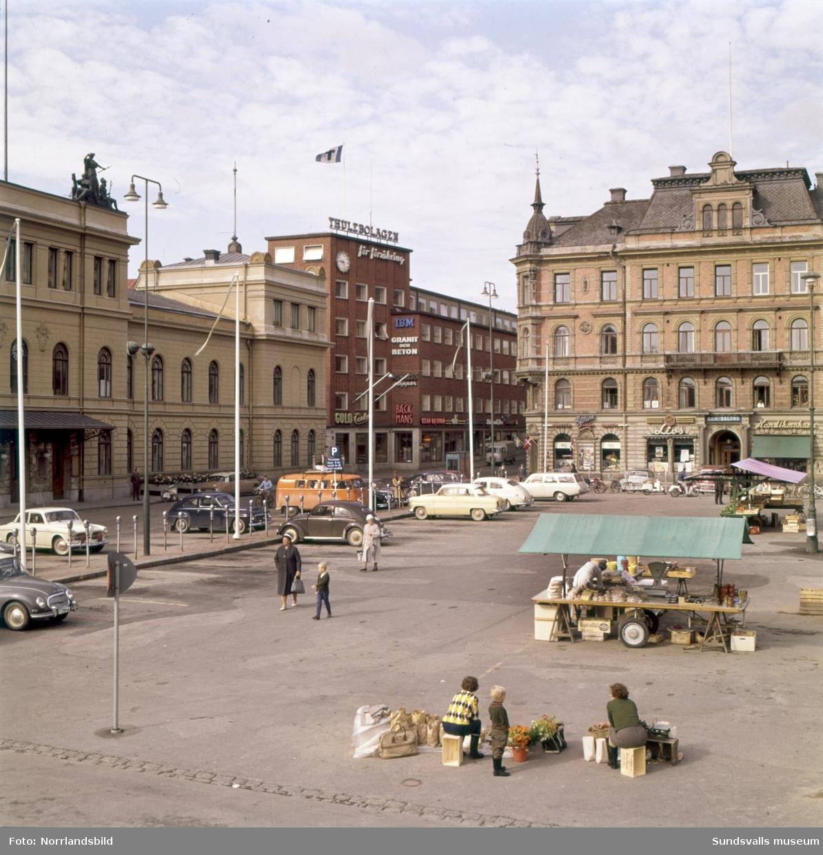 Stora torget med torghandel. Sjöléns färghandel syns i hörnet av Hirschska huset mot Stadshuset och Thulehuset och på den andra bilden är det full kommers hos Ivans blommor.
