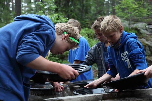 Barn som vasker sølv ut av panner. (Foto/Photo)