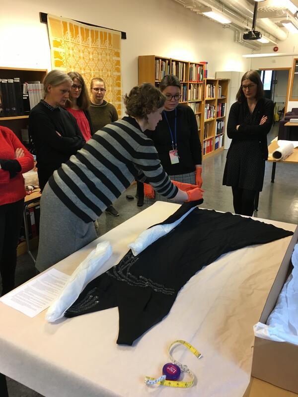 kvinne som pakkar inn tekstil i silkepapir medan andre ser på (Foto/Photo)
