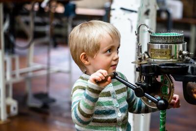 blond gut med stripete strikkegenser sveivar på maskin. Foto/Photo