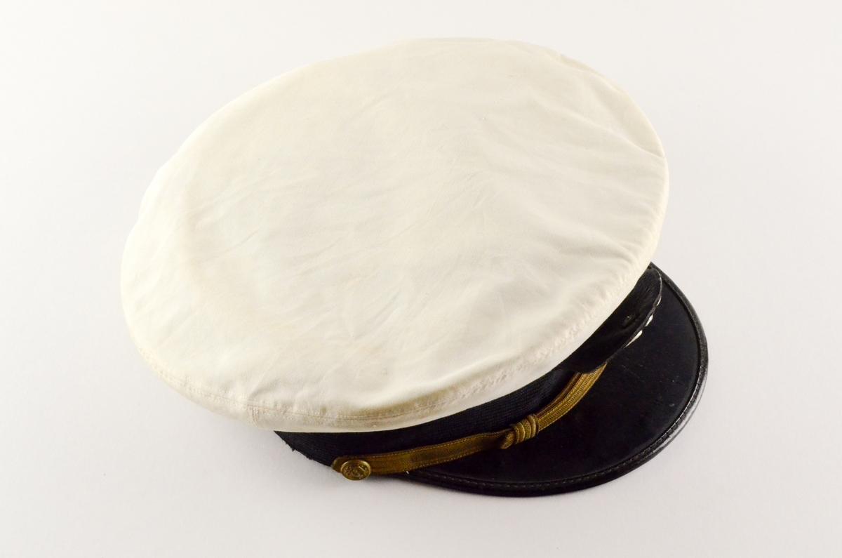 Uniformslue med skygge. Hvit rund flat pull, sort hattebånd med påsatt gulltråd, tynnere i front. Midt foran på pull og bånd: emblem i metall; sølvfarget ørn på lfagg, gullfargede anker. Sort skygge. Kanten stivet innvendig med brunt lærbånd.