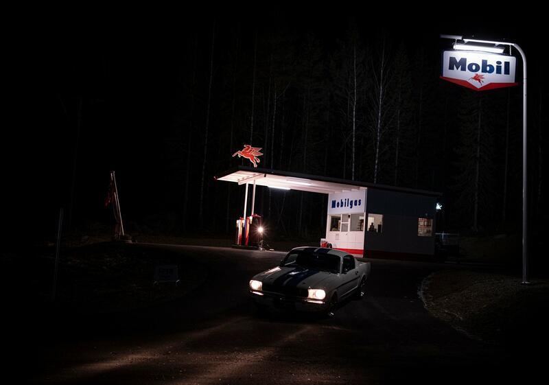 Novembermørket gir en mystisk ramme for øde, opplyst bensinstasjon og bil i mørket. Foto: Morten Reiten/Norsk vegmuseum (Foto/Photo)
