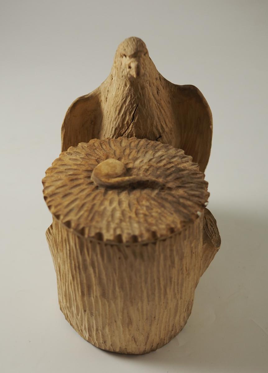 Ørn og krukke skåret i tre med grove, enkle redskaper. Ei pipe er skåret på lokket til krukka.