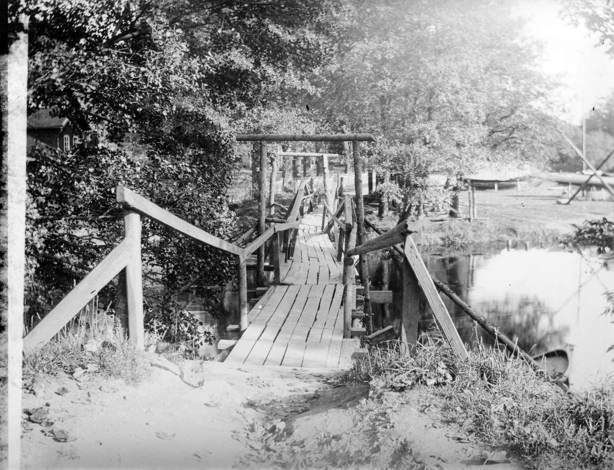 Träbro över Säveån i Lugnet. Mellan trädens löv till vänster syns en del av ett hus. Till höger om bron ligger en eka och i bakgrunden syns en båt uppe på land.