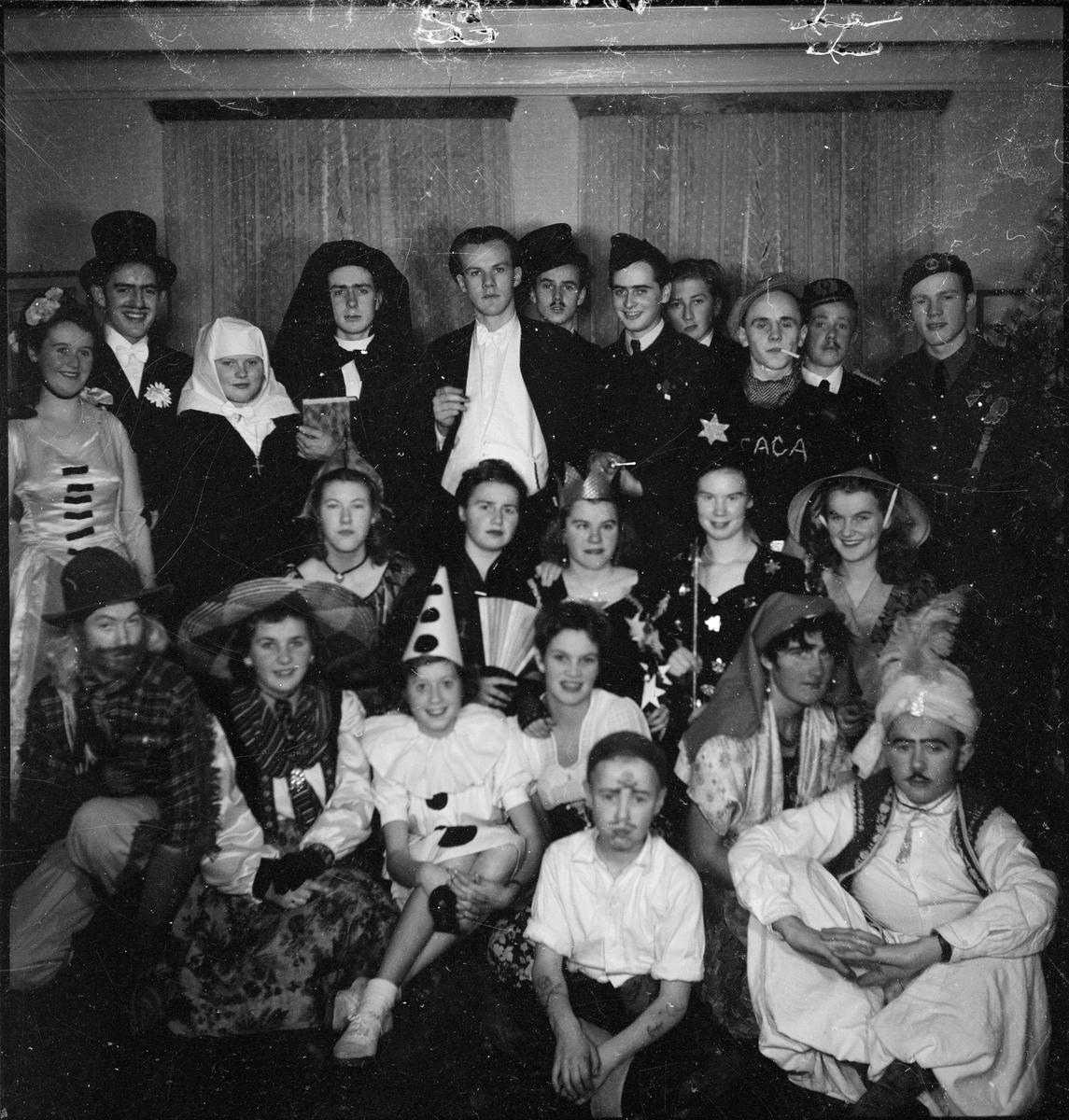 En gruppe med karnevalskledde unge voksne i selskap.