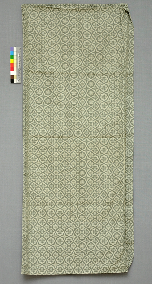 """Madrassvar av grönt stjärnbolstertyg i bomull. Sammansatt av fram- och bakstycke med en 70 mm bred kant på tre sidor. En långsida öppen. Avgränsande innertyg av tunn bomull fastsytt i sicksack omväxlande i ovan- och undersidan med 140 mm mellanrum. Märkt med initialerna """"BE"""" i röda stjälkstygn i ena hörnet."""