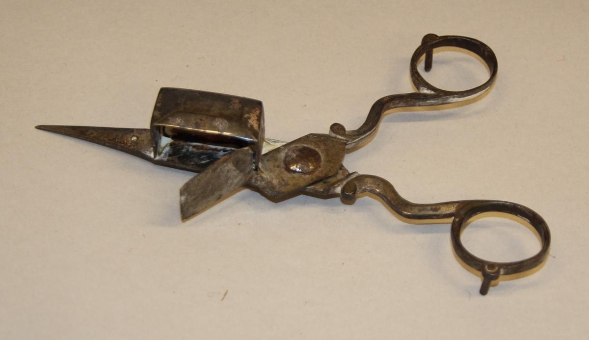 Veikesaks i metall, to små tappar på undersida, slik at ein kan legge frå seg saksa på eit bord el.