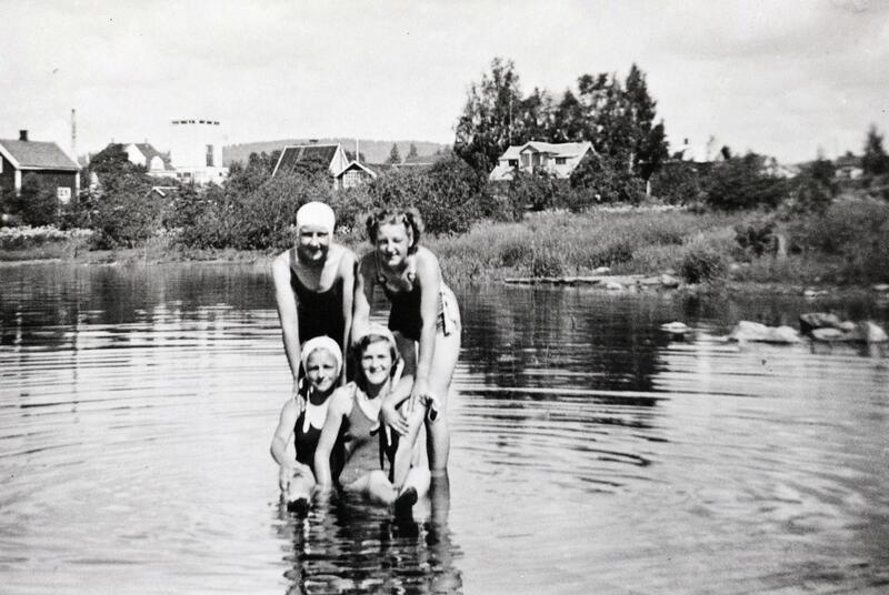Svart-hvitt foto av fire unge damer med badedrakt og badehette ute i Mjøsa. (Foto/Photo)