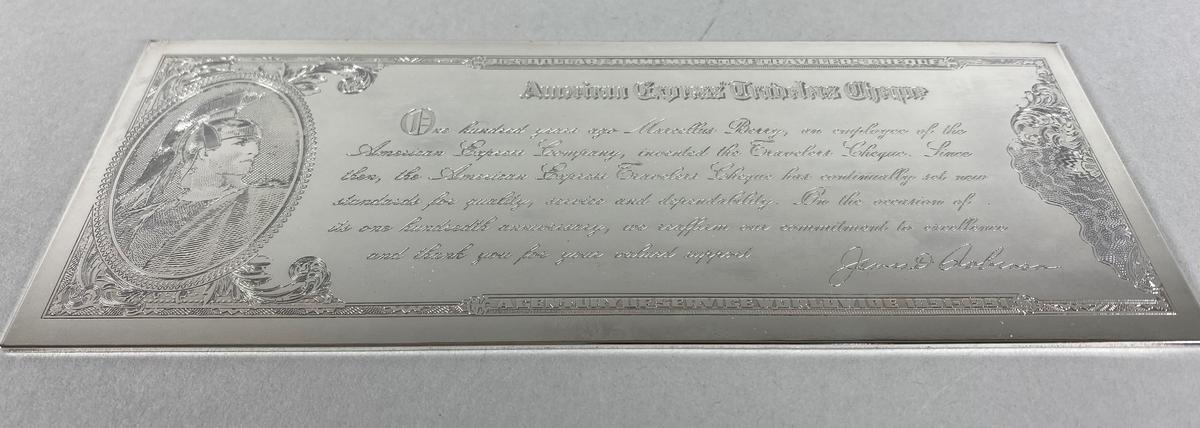 Gravert, tynn plate av sølv med tekst og motiv både på fremside og bakside, utformet som en reisesjekk. Platen ligger i en eske med lokk. Esken er lilla og er kledd i mykt stoff.