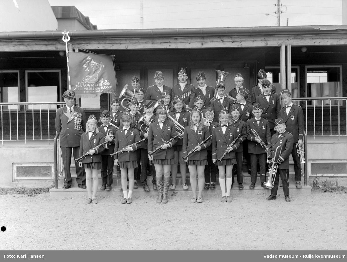 Vardø guttemusikkorps ved inngangen på Sentrum skole i Vadsø 30.juni 1969. På bildet er det både gutter og jenter blant korpsmedlemmene.