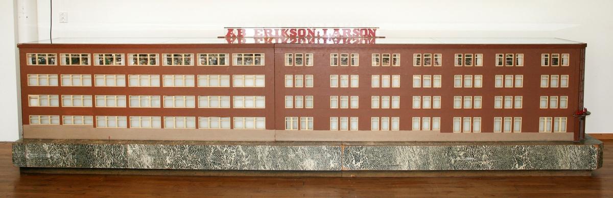 """Modell. """"Erlamontern"""". Visar sysalen inne i fabriksbyggnaden, på AB Eriksson & Larsson. På ovansidan, under en glasskiva, visas en produktionslinje med tillskärningsavdelning, sömnad och ångning. Figurerna drivs med el.   AB Eriksson & Larsson tillämpade momentsömnad, vilket innebär att sömmerskorna sydde sina egna moment. I folkmun kallades fabriken """"Erlabolaget"""".  Modellen tillverkades, av företagets ingenjör Jöns Koch och hans hustru, till Borås mässan 1949."""