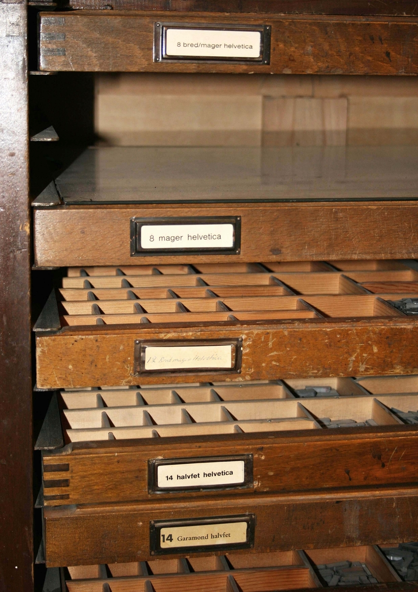 Skåp i brunbetsat trä. Fyrsidigt, öppet framtill. Fack för 20 lådor, 8 finns. Varje låda, märkt med namnet på typsnittet med en pappersetikett. Typerna av gjutet bly. Lådorna med svartlackerade draghandtag märkta: DAHLBERG  Funktion: Förvaring av typer. Användes för att bilda ord och meningar på ett pappersark  Familjeföretaget AB J.F. Björsell startades 1888 i Borås av Johan Fredrik Björsell och var verksamt inom kontorsvaru- och tryckeribranschen. Johan Fredrik Björsell efterträddes av sin son Allan Björsell.  1965 övertog Anders och Åke Björsell ledningen av bolaget, som 1997 såldes till ett holländskt företag.