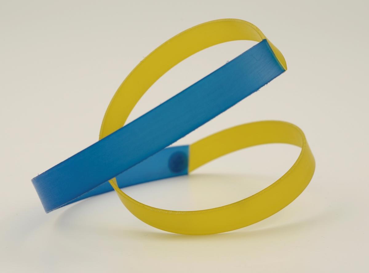 Armbånd laget av stive nylonbånd som er cirka 1 cm brede. Til en blå bue er det festet et gult tvunnet bånd.