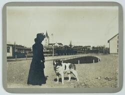 """En kvinna med en hund, """"Baron"""". Nora kyrka i bakgrunden.  Fo"""
