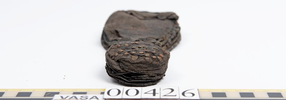 Del av skobotten bestående av tre sulor mellan vilka klacklappar sitter fästade med skopligg. På skobottnens undersidan sitter en klacklapp och en halvmånformad laglapp fästad med skopligg. Yttersulan är ritsad. Lädret är klibbigt.