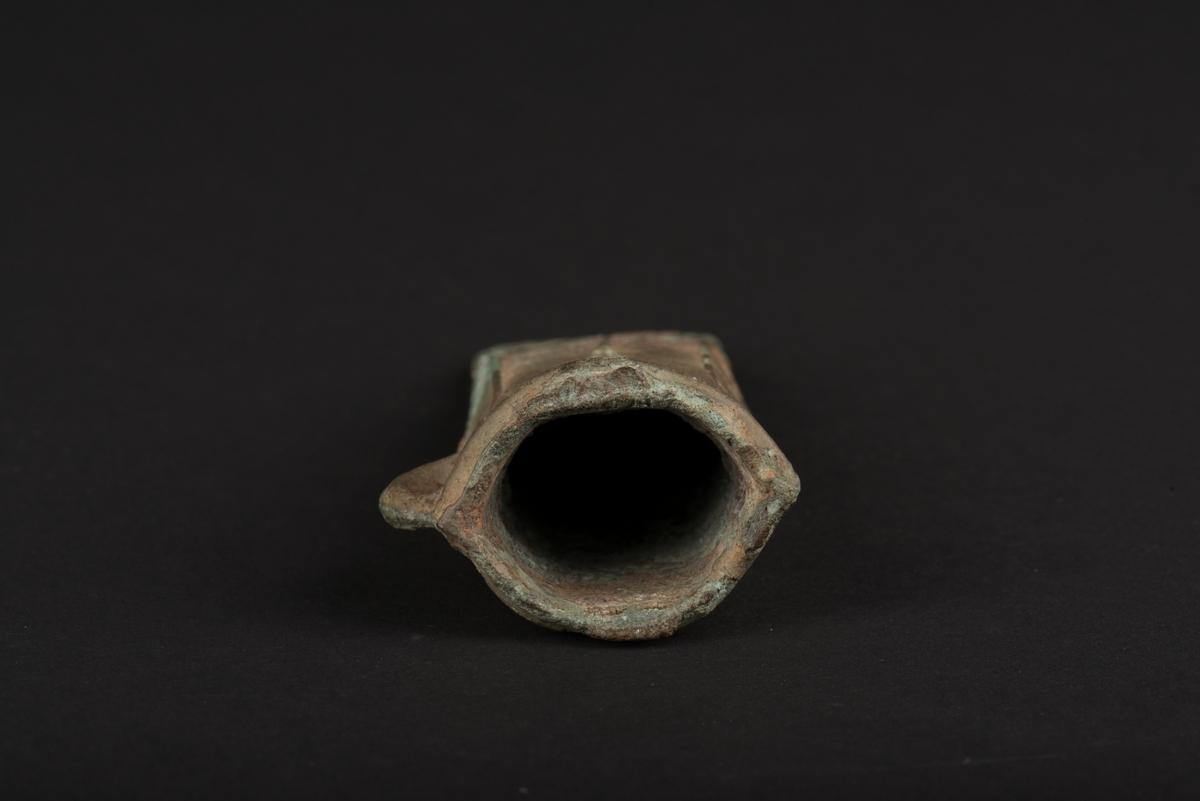Holkyxa av brons. Oval holköppning med en ås runt kanten. Åsar på sidorna som bildar ett mönster. På undersidan en ögla. Synliga gjutsömmar.