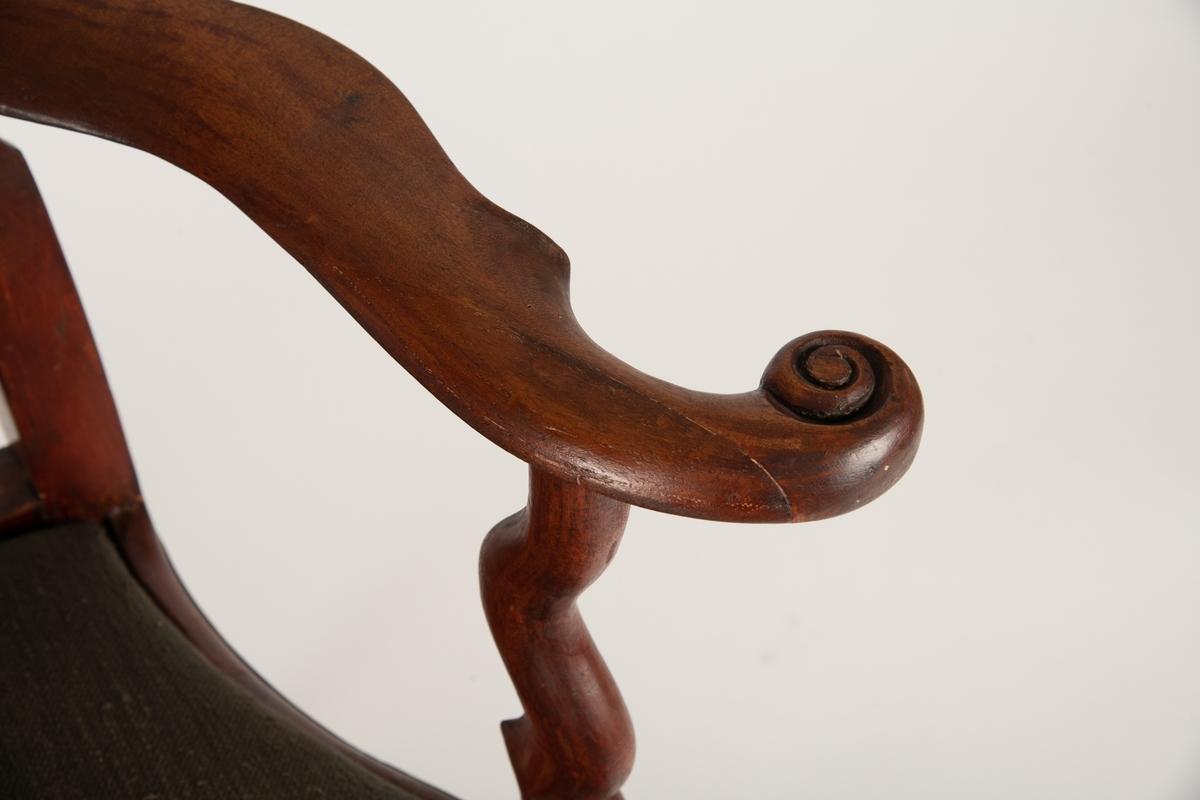 Høy, åpen, svungen rygg med balusterformet midtbrett,  toppstykke utskåret med skjell og blad. Løst sete  nedfelt i sargen, stoppet med sjøgress, trukket med blomstret trekk (ca. 1910). Svungne armlener.  Tunget sarg med skjell og blad utskåret i fronten,  svungne ben med skjell-løv på kneet, spiss fot.  Ingen bindeledd mellom benene.