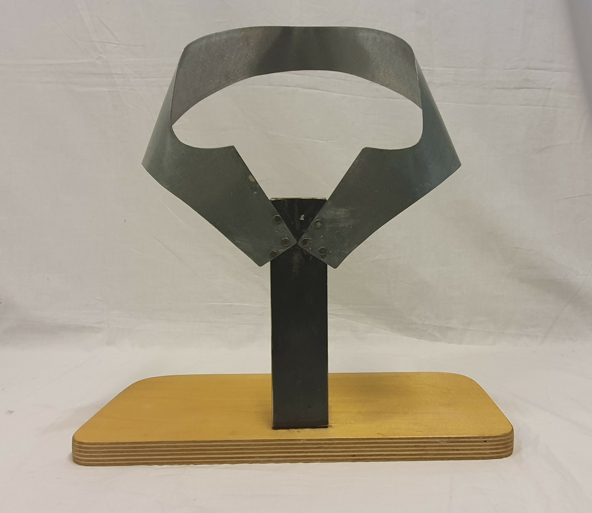 Stativ laget av givers ektefelle; Olav Solvang. Stativet brukes til å forme bordpapp til valk. Bordpapp settes i stativet for å tørke og få formen.